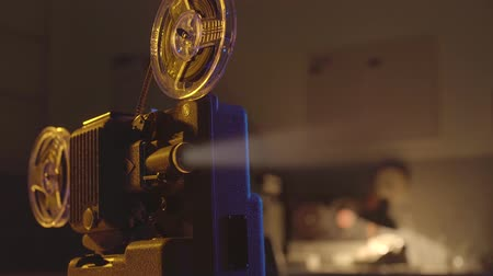 устаревший : Vintage old fashioned projector in a dark room projecting a beam of light, cinematography concept