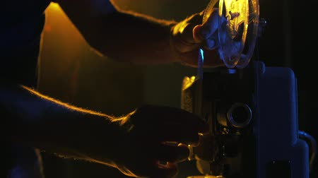 cinematography : Operator adjusting filmstrip on the vintage projector in a dark room Stock Footage