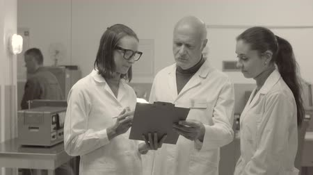 inventor : Scientific team meeting in laboratory and discussing project results together, vintage style Stock Footage
