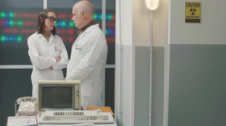 inventor : Scientific team working in the laboratory and discussing together, sci-fi computer with leds in the background, vintage style Stock Footage
