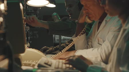 устаревший : Vintage sci-fi working in a room: they are sitting at desk, answering phone calls, using computers and making radio transmissions