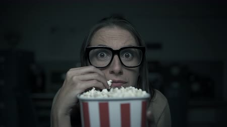 ijesztő : Scared woman watching horror movies at home and eating popcorn