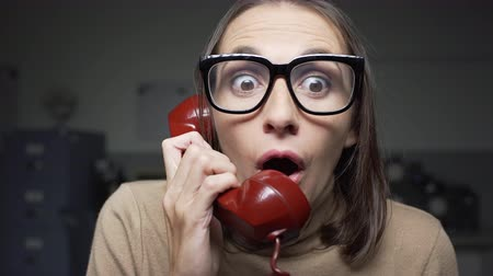 secretário : Shocked woman on the phone, she is receiving unexpected surprising news from her friend