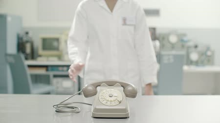 döner : Confident female scientist in a laboratory, she is pushing away an old obsolete rotary dial telephone Stok Video