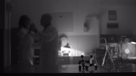 atomic model : Scientists dancing together in the laboratory and scientific equipment in the foreground Stock Footage