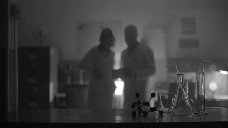 устаревший : Scientists working together and discussing in a dark vintage style lab, scientific equipment in the foreground