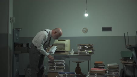 administracja : Office worker searching for files in his messy office with piles of paperwork: business management and administration concept, video montage