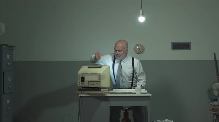 устаревший : Angry mature businessman sitting at desk and hitting his outdated old computer Стоковые видеозаписи