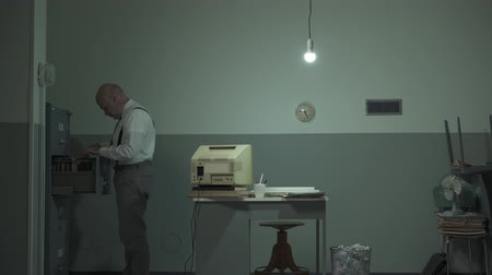 yıkık : Vintage style mature businessman working in his office, is using an outdated computer, searching for files and trashing a document, video montage Stok Video