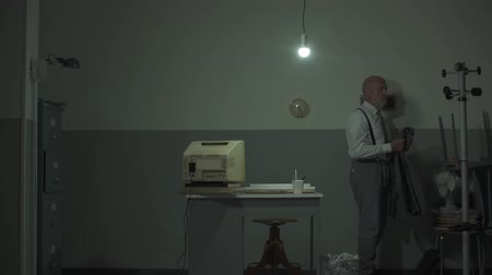 устаревший : Sad office clerk arriving in his office: he turns his light on his jacket and starts working Стоковые видеозаписи