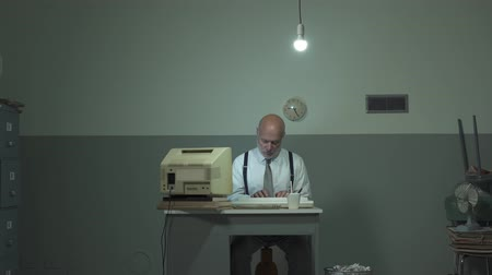 устаревший : Corporate businessman working in a rundown office, he is using an outdated computer