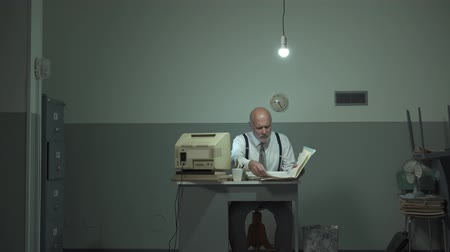 yıkık : Corporate businessman sitting at desk and working in a rundown office, he is checking paperwork in a file Stok Video