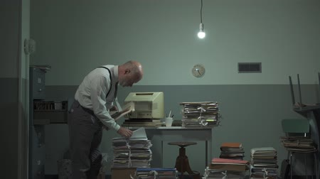 yıkık : Disorganized businessman searching for files in his office, he is surrounded by piles of paperwork, management and planning concept