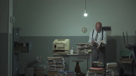 rendetlenség : Disorganized businessman searching for files in his office, he is surrounded by piles of paperwork, management and planning concept