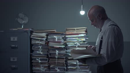 byrokracie : Serious businessman reading a document in the office, piles of paperwork in the background
