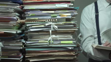 byrokracie : Corporate businessman overloaded with paperwork, he is reading a file and browsing pages Dostupné videozáznamy