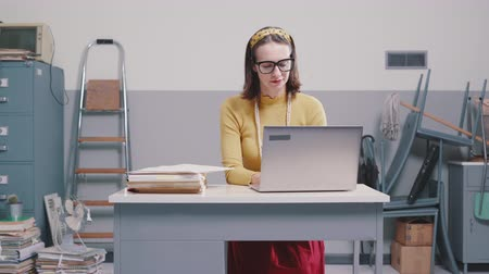 secretária : Vintage style secretary working in a messy office, she is using a laptop and writing Stock Footage