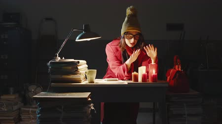 stacks : She is wearing a coat and warming her hands on burning candles
