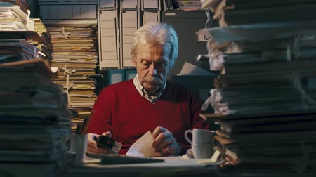 устаревший : Senior clerk sitting at desk and doing a boring repetitive job surrounded by piles of files, he is stamping paperwork