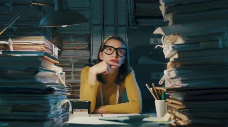burocracia : Young businesswoman sitting at office desk and thinking with hand on chin, she is surrounded by piles of paperwork Stock Footage