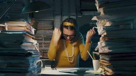 перегружены : Happy cheerful woman celebrating a business meeting with her fists, she is surrounded by piles of paperwork