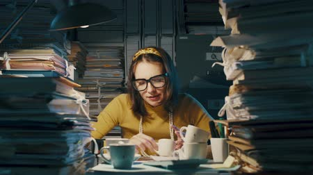 adminisztratív : Nervous office clerk shaking after drinking too many coffees, she is working overtime and overloaded with paperwork Stock mozgókép