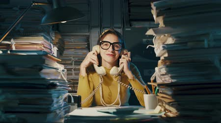 administracja : Smiling business woman answering phone calls in office, she is holding two telephone receivers and nodding Wideo