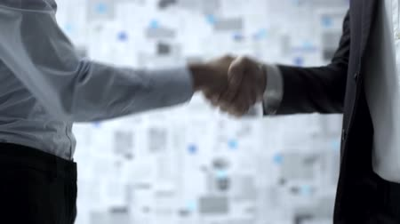 beyaz yakalı işçi : Corporate business people meeting and shaking hands, wall covered with financial reports in the background Stok Video