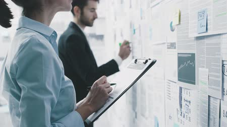 panoya : Corporate business people working together, they are checking reports and financial data on a wall: business management concept Stok Video