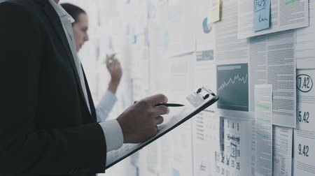 toezicht : Corporate business people working together, they are checking reports and financial data on a wall: business management concept Stockvideo