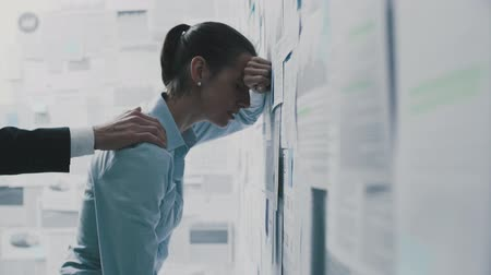 çöküş : Depressed exhausted businesswoman leaning on a wall covered with financial reports and colleague supporting her: business failure and crisis concept Stok Video