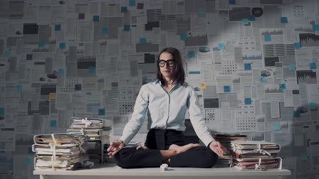 temper : Corporate businesswoman practicing meditation and yoga in her office