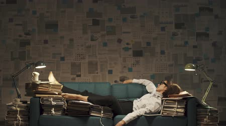 перегружены : Exhausted businesswoman sleeping on the couch, she is surrounded by piles of paperwork