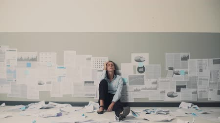 перегружены : Desperate businesswoman sitting on the floor surrounded by crumpled paperwork: business failure and crisis concept