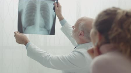 examining : The doctor examining the womans radiography and talking Stock Footage