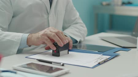 doença : Doctor stamping a prescription for female patient, medical records and treatment concept