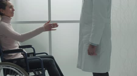 paraplegic : Professional doctor shaking hands with patient in wheelchair, she is smiling at him