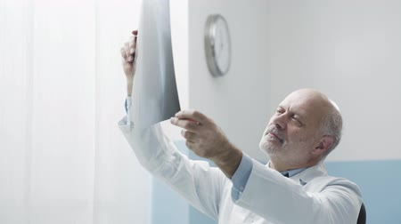 x ray image : Professional senior radiologist in the office, looking at patients x-ray film
