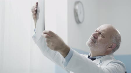 imagem : Professional senior radiologist in the office, looking at patients x-ray film