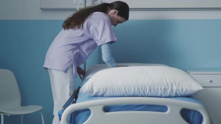 подопечный : Professional nurse working at the hospital: she is making the bed and tidying up the room, medical staff concept