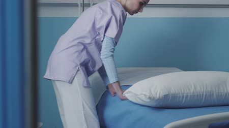 assistência : Professional nurse working at the hospital: she is making the bed and tidying up the room, medical staff concept