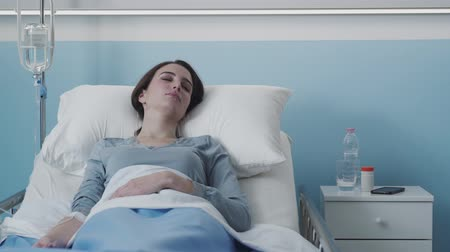 salt bed : Young female patient lying in bed at the hospital and getting IV therapy, medical treatment concept Stock Footage