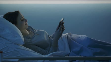 alfabeto : Young woman lying in a hospital bed at night, she is connecting online using a digital tablet and smiling Vídeos
