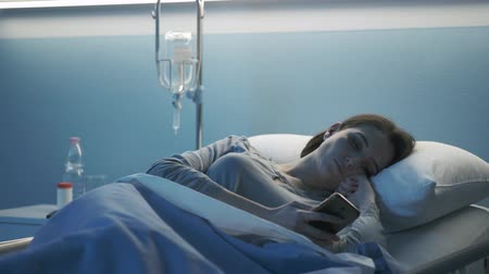 infusion : Hospitalized patient lying in bed at the clinic, she is worried and chatting with her smartphone Stock Footage