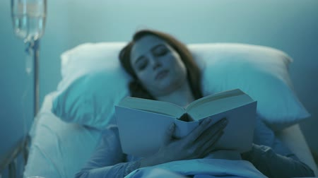 chirurgia : Young female patient lying in a hospital bed at night, she cant sleep and she is reading a book