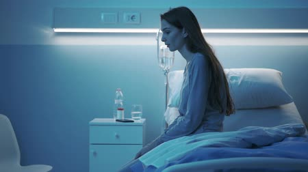 preoccupazione : Young lonely woman sitting on the hospital bed at night, she cant sleep and she is feeling sad
