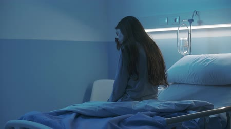 preoccupazione : Young lonely woman sitting on the hospital bed at night, she is worried and sleepless
