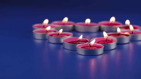 knot : Twelve pink scented candles burn on a table with a blue background. They are in small iron candle holders. Focus in the foreground.