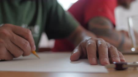 Artist with green shirt sketching with pencil on paper with daylight