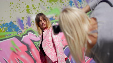 Model with pink dress posing in front of graffiti during a photo session